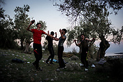 A group of young refugees from Afghanistan is seen dancing on the top of a hill not far from the moria refugees camp. Many families lives in a makeshift camp outside Moria camp living in tents in a olives trees plantation. About 8500 migrants and refugees are living in hard condition on the island of Lesvos, many of them outside the organized camp. Moria, Greece. December 12th 2017.