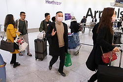 © Licensed to London News Pictures. 22/01/2020. London, UK. Passengers wearing face masks arrive at Heathrow airport after China Southern Airlines flight CZ673 from Wuhan arrives in London. The Coronavirus virus has originated in the Wuhan region. Photo credit: Ray Tang/LNP
