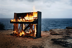 """Dresden Piano, Avalon Beach Sydney,Photo of Piano on Fire against the ocean,photography by paul green, musical instrument series, this piano had been made in Dresden Germany in about 1900,it had found its way to Sydney where it had been used in the bars and clubs of Kings Cross, the bohemian and red light district of Sydney,it had big wheels attached to the bottom to move it from venue to venue and a very avant guarde paint job. It had """"dresden Piano"""" stamped on its iron frame.exhibition image once hung in the Piano room nightclub in Kings Cross Sydney. original print now missing"""
