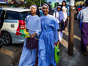 27 NOVEMBER 2017 - YANGON, MYANMAR:  Catholic nuns on the street in Yangon after the Pontiff's arrival in Myanmar. Pope Francis arrived in Yangon Monday for a four day / three night visit. Tuesday he is going to the capitol, Naypyidaw (Nay Pyi Taw) to meet with Aung San Suu Kyi and other Myanmar leaders. Wednesday and Thursday he is saying mass in Yangon and on Thursday afternoon he is going to neighboring Bangladesh. There are around 450,000 Catholics in Burma, about 1% of the total population.   PHOTO BY JACK KURTZ