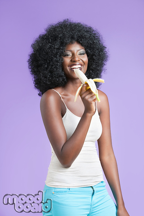 Happy stylish young woman eating banana against violet background