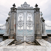 A gate opening to the Bosphorus Strait at Dolmabahçe Palace. Dolmabahçe Palace, on the banks of the Bosphorus Strait, was the administrative center of the Ottoman Empire from 1856 to 1887 and 1909 to 1922. Built and decorated in the Ottoman Baroque style, it stretches along a section of the European coast of the Bosphorus Strait in central Istanbul.