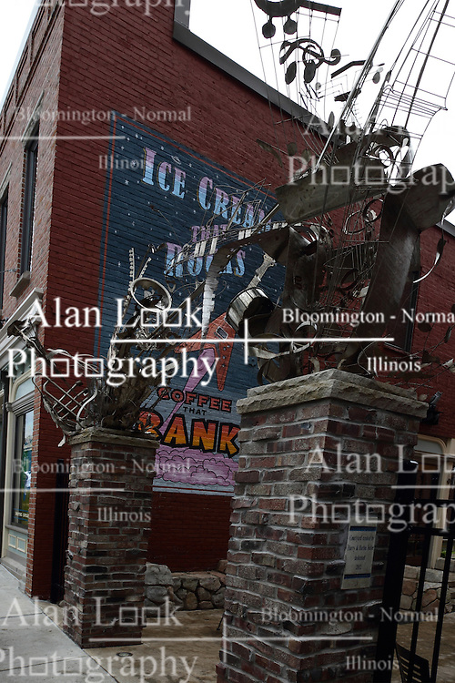 11 July 2015:  Resident metal sculptures and mural on the side of a building in Uptown Normal at the entrance to a small comfort courtyard area created by Harry and Barbie Fuller.  Shot at the  2015 Sugar Creek Arts Festival in Uptown Normal Illinois