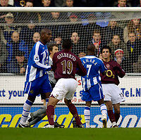 Photo: Jed Wee.<br />Wigan Athletic v Arsenal. The Barclays Premiership.<br />19/11/2005.<br />Wigan's Henri Camara squares up to Arsenal's Cesc Fabregas (R) in the aftermath of the first Wigan goal.