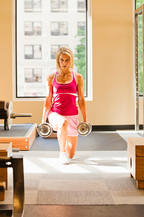 Woman doing dumbell lunges in a health club / gymnasium.