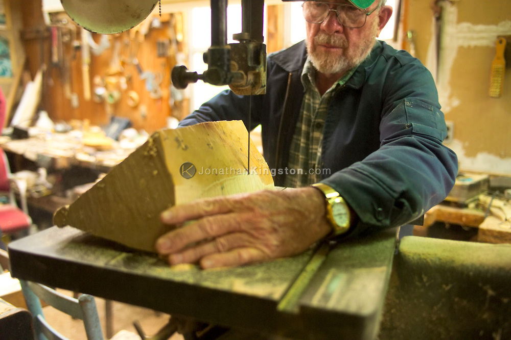 """FLOYD, VA,  Arthur Conner, a renowned fiddle maker in both the bluegrass and classical music worlds, cuts away slices of wood to inspect them for insect damage in Floyd, Virginia.  """"You can't make a good fiddle without good wood"""".  Many musicians at the country store play on Arthur Conner's fiddles."""