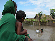 Flood victim Fatema Biwi sits on a high place, near their submerged house and holds her son Habibur, as her daughter is bringing drinking water at Motir village, about 313 kilometers southwest of Gauhati, the capital city of Northeastern Indian state, Assam, Monday, June 28, 2004. ..Floodwaters of the Asia'a one of the largest river, Brahmaputra and its 35 tributaries have affected more than one million in all of Indian subcontinent and disrupted communication in many parts of the India and Bangladesh, sources said.  (AP Photo/ Shib Shankar Chatterjee)