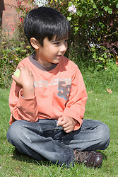 Little boy sitting playing with a ball in the garden,