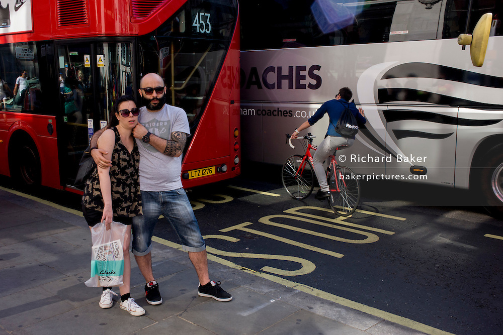 Hugging couple and urban cyclist leaning against a tour coach in central London.