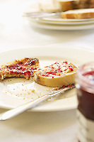 Half-eaten toast with jam on plate with butter knife close-up