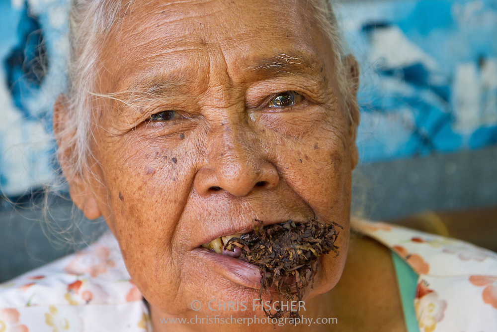 Elderly woman chewing tobacco at the Ngasem Bird Market, Yogyakarta, Central Java, Indonesia.