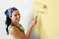 Woman applying yellow paint to interior wall elevated view