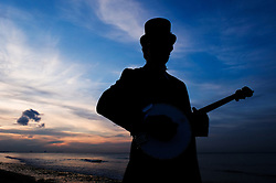 © Licensed to London News Pictures.20/08/15<br /> Saltburn, UK. <br /> <br /> PAUL BALDWIN, a banjo player with the Jet Set Border Morris Dancers plays on the beach at Saltburn during sunset.<br /> <br /> Photo credit : Ian Forsyth/LNP