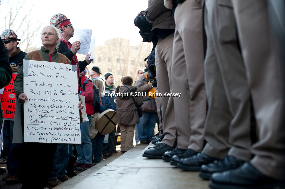 "Retired teacher Cecile Stelzer-Johnson (L) waits outside of the state Capital as police bar access to the building on March 1, 2011 in Madison, Wisconsin. Despite a court order issued Tuesday mandating that the state Capitol should be opened to the public ""during business hours and at times when governmental matters, such as hearings, listening sessions and court arguments are being conducted"" the Capitol remained closed to the public.  (Photo by Brian Kersey)"