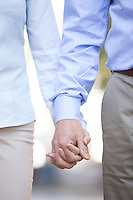 Midsection of middle-aged couple holding hands outdoors
