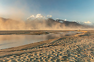 High winds create clouds of sand along the Chilkat River in Southeast Alaska. Winter. Morning.