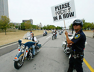 Milwaukee motor officer Gregg Duran (R) directs motorcycles arriving for the final Harley-Davidson party in downtown Milwaukee August 31, 2003.  The legendary American motorcycle company celebrated its 100th anniversary over four days.       REUTERS/Rick Wilking