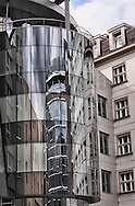 A modern Glass Building next to old Architecture in Prague, with the opposite Building mirroring in the Glass Building.