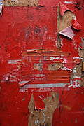 Detail close-up of fire escape sign on a hoarding made from plyboard, with torn paper covering of red material. Caton St, WC1