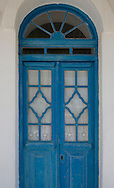 A traditional blue painted wood door with lace curtains in Pano Petali, Sifnos, The Cyclades, Greek Islands, Greece, Europe