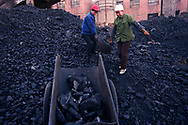 Workers at the state run Jinhuagong coal mine sorts coal outside the mine. Seven of the world's ten most polluted cities are in China due primarily to China's dilapidated heavy industries and its dependence on coal - the dirtiest form of energy. 75% of China's growing energy needs comes from coal. <br /> D&agrave;t&oacute;ng, Shanxi Province, China. 10/11/2005<br /> Photo &copy; J.B. Russell
