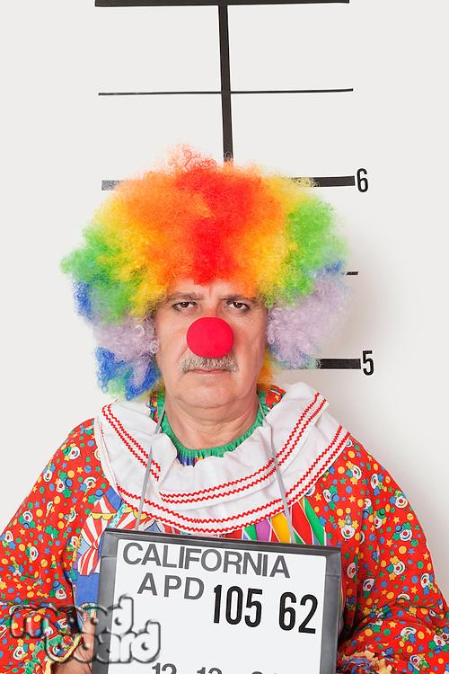 Portrait of senior clown posing for mug shot