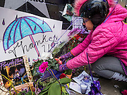 "22 APRIL 2016 - MINNEAPOLIS, MN: MINA LEIERWOOD, from Minneapolis, MN, leaves a thank you card at a memorial for Prince in front of 1st Ave in Minneapolis. She said listened to Prince's music all through high school. Thousands of people came to 1st Ave in Minneapolis Friday to mourn the death of Prince, whose full name is Prince Rogers Nelson. 1st Ave is the nightclub the musical icon made famous in his semi autobiographical movie ""Purple Rain."" Prince, 57 years old, died Thursday, April 21, 2016, at Paisley Park, his home, office and recording complex in Chanhassen, MN.    PHOTO BY JACK KURTZ"
