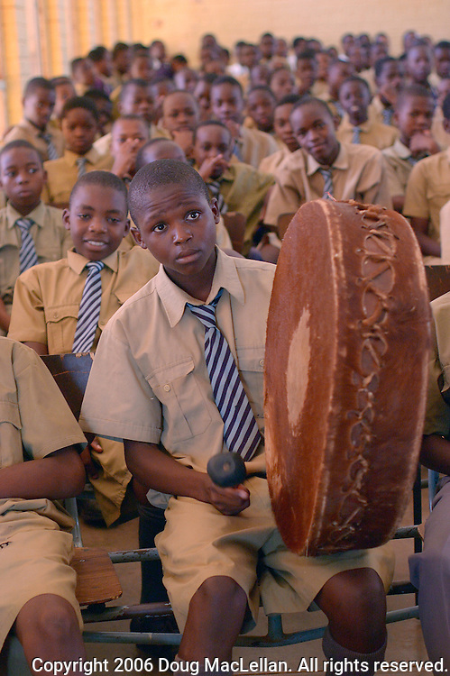 A High School boy plays a large drum at the last assembly before Christmas holidays. Howard Collegiate Institute, Mashonaland Central, Zimbabwe, 2006.
