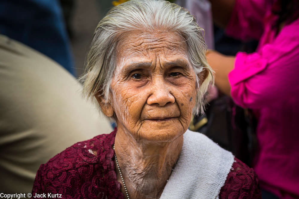 """22 JULY 2013 - PHRA PHUTTHABAT, THAILAND: An elderly woman at the Tak Bat Dok Mai at Wat Phra Phutthabat in Saraburi province of Thailand, Monday, July 22. Wat Phra Phutthabat is famous for the way it marks the beginning of Vassa, the three-month annual retreat observed by Theravada monks and nuns. The temple is highly revered in Thailand because it houses a footstep of the Buddha. On the first day of Vassa (or Buddhist Lent) people come to the temple to """"make merit"""" and present the monks there with dancing lady ginger flowers, which only bloom in the weeks leading up Vassa. They also present monks with candles and wash their feet. During Vassa, monks and nuns remain inside monasteries and temple grounds, devoting their time to intensive meditation and study. Laypeople support the monastic sangha by bringing food, candles and other offerings to temples. Laypeople also often observe Vassa by giving up something, such as smoking or eating meat. For this reason, westerners sometimes call Vassa the """"Buddhist Lent.""""     PHOTO BY JACK KURTZ"""