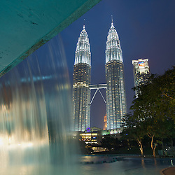 The waterfall from an adjacent water park frames the Petronas Towers in Kuala Lumpur, Malaysia.