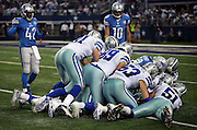 A group of Dallas Cowboys players jump on a loose ball during the NFL week 18 NFC Wild Card postseason football game against the Detroit Lions on Sunday, Jan. 4, 2015 in Arlington, Texas. The Cowboys won the game 24-20. ©Paul Anthony Spinelli