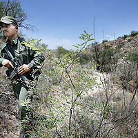 Verenigde Staten.Arizona.Nogales.juli 2005.<br /> Grenspolitie arresteert illegalen in de woestijn van Zuid Arizona, die illegaal vanuit Mexico de Verenigde Staten zijn binnengekomen. Ze worden gefoullerd op wapens en hun papieren worden gecontroleerd. Daarna worden de illegalen naar het hoofdbureau van de grenspolitie getransporteerd, waarna ze geregistreerd worden alvorens ze terug de grens overgebracht worden.<br /> Op de foto een  gewapende agent van de grenspolitie op speurtocht naar illegalen in de woestijn.Bewapend.Machinepistool.Jagen.Border Patrol.Zoektocht.Illegale vluchtelingen.Droogte.Greansproblematiek.Mexicanen.<br /> Archives 2005. Chase by police on illegal Mexicans who cross the border in Arizona.