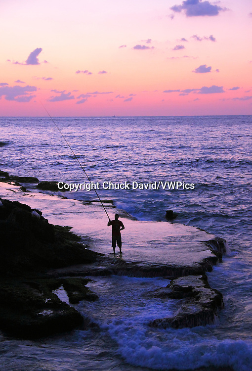 A lone fisherman casts his rod along Beirut's rocky Mediterranean shoreline at sunset, Lebanon.