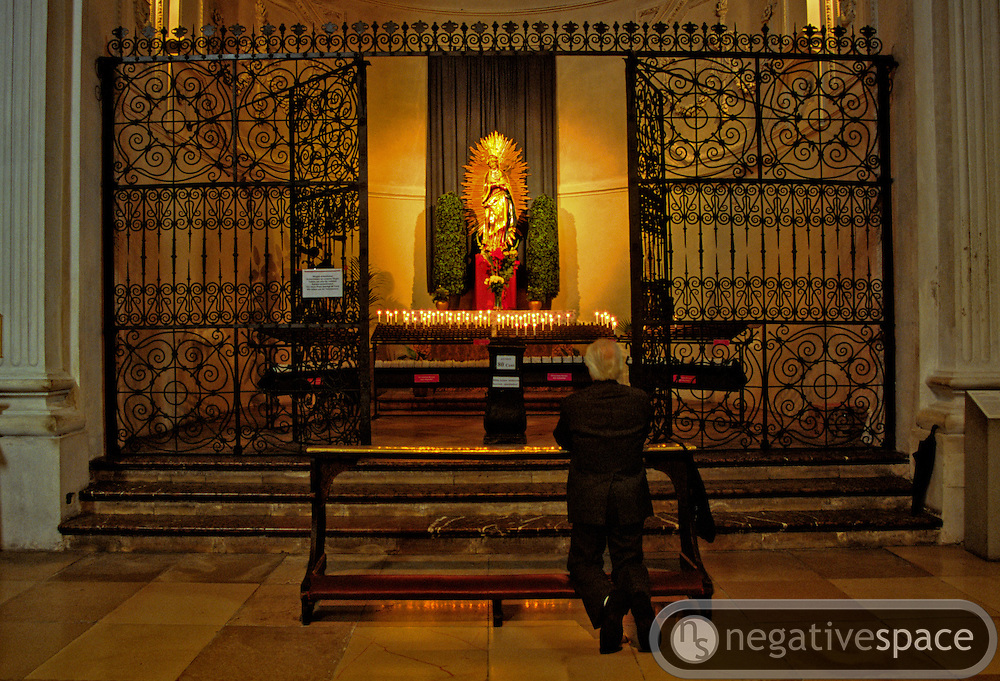 Praying before a shrine at the Theaterinerkirche, Munich, Germany