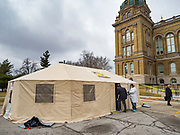 "16 MARCH 2020 - DES MOINES, IOWA: A public health employee in protective clothing helps a person into a health screening tent on the east lawn at the Iowa State Capitol in Des Moines. Because of numerous reports of Coronavirus in Iowa, the governor is suspending the legislative session for 30 days. It was scheduled to run until mid-April. Sunday night, the Governor announced that the state health department had recorded ""community spread"" in Des Moines. As a result the State Capitol instituted mitigation measures that included mandatory health screening for everyone going into the building, canceling group tours of the building, and closing the souvenir shop and snack bar..      PHOTO BY JACK KURTZ"
