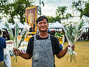22 OCTOBER 2016 - BANGKOK, THAILAND:  A flower vendor sells flowers to mourners on Sanam Luang in Bangkok. Sanam Luang, the Royal Ceremonial Ground, was packed Saturday with more than 100,000 people mourning the Monarch's death. The King died Oct. 13, 2016. He was 88. His death came after a period of failing health. Bhumibol Adulyadej was born in Cambridge, MA, on 5 December 1927. He was the ninth monarch of Thailand from the Chakri Dynasty and is also known as Rama IX. He became King on June 9, 1946 and served as King of Thailand for 70 years, 126 days. He was, at the time of his death, the world's longest-serving head of state and the longest-reigning monarch in Thai history.      PHOTO BY JACK KURTZ