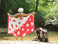 Young woman standing by lake wrapping with sarong back view