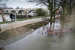 © Licensed to London News Pictures. 02/04/2018. London, UK. A cyclist passes rising floodwater at Deer Park next to Richmond Lock.  Heavy rain has caused some flooding in areas near the River Thames in the south. Photo credit: Peter Macdiarmid/LNP