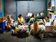 29 FEBRUARY 2016 - BANGKOK, THAILAND: Sidewalk vendors in the Bangkok flower market relax early Monday. Many of the sidewalk vendors around Pak Khlong Talat, the Bangkok flower market, closed their stalls Monday. As a part of the military government sponsored initiative to clean up Bangkok, city officials announced new rules for the sidewalk vendors that shortened their hours and changed the regulations they worked under. Some vendors said the new rules were confusing and too limiting and most vendors chose to close Monday rather than risk fines and penalties. Many hope to reopen when the situation is clarified.    PHOTO BY JACK KURTZ
