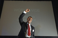 Business man speaking at conference, arm raised