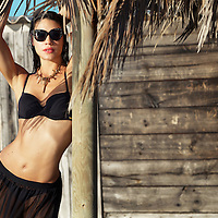 Caucasian female model wearing black swimwear and sunglasses standing outdoors in summer