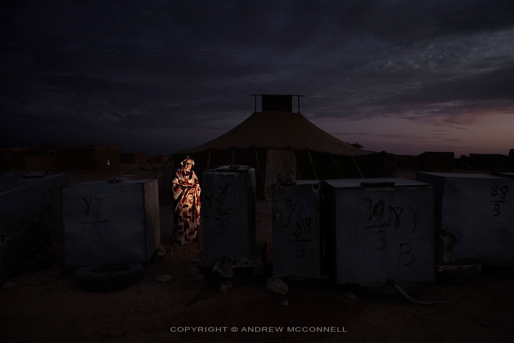 Sana Zrog, 19, student, pictured beside water tanks in El Aaiún refugee camp, Algeria...When I was seven my parents told me we were living in a refugee camp, I was surprised and sad that I didn't know my homeland. I knew then that I didn't want to spend my life here or have my children here. When I was fifteen I started studying in Libya. When I went there I wished Sahara could be like Libya, with buildings and roads and a good quality of life. I finished secondary school there and now I am in University studying economics. I am home now for a holiday but tomorrow I will fly back to Libya. Everything is free; the flight, accommodation, clothes, books, food, even toothbrushes, shampoo and some money every month. I say thank you to Libya for this, they help the Saharawis. All Saharawi students can go to university in Libya, Algeria or Cuba. ..It makes me sad that when I return from Libya with a degree I will probably not find a job. But my degree is for the future. I hope I can have a job in my homeland when we have independence. I prefer peace. I think the Saharawis must wait more years, we have waited for thirty four years and we can wait another thirty four years. But if the United Nations does not solve anything we must fight.