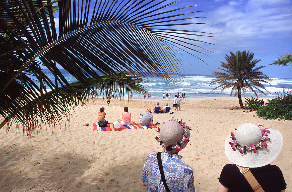 Tourists visit Sunset Beach, a well-known surf-break on the North Shore of the island Oahu in Hawaii.