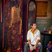 A temple volunteer rests during the week festival of the nine emperors.