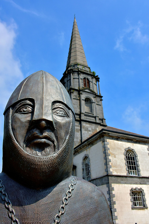 Strongbow Statue and Christ Church Cathedral in Waterford, Ireland<br /> In 1167, Dermot MacMurrough was overthrown as the King of Leinster.  In retaliation, he recruited mercenaries to reclaim his title.  The leader of the Norman invasion was this distinguished medieval knight wearing a nasal helmet.  His name was Richard de Clare, the 2nd Earl of Pembroke.  He was commonly called Strongbow. This bronze statue, along with one of his wife, was sculpted by Eithne Ring. They sit together on their thrones in front of the Christ Church Cathedral.