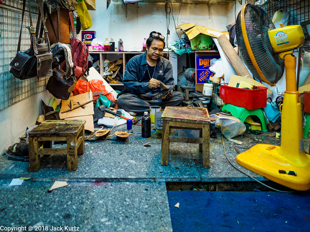 17 SEPTEMBER 2018 - BANGKOK, THAILAND: A cobbler repairs shoes in his stall in the Klong San market, next to the ICONSIAM development. ICONSIAM is a mixed-use development on the Thonburi side of the Chao Phraya River. It is expected to open in 2018 and will include two large malls, with more than 520,000 square meters of retail space, an amusement park, two residential towers and a riverside park. It is the first large scale high end development on the Thonburi side of the river and will feature the first Apple Store in Thailand and the first Takashimaya department store in Thailand. Rents for shopkeepers in Klong San market can be up to 30,000 Thai Baht per month (about $920US) and some in Bangkok are concerned that Klong San Market will lose its local character when the huge mall opens.    PHOTO BY JACK KURTZ