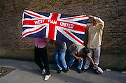 name of their favourite football club. During a street party in London's East End, the young men have decided to parade outside with their flag to show their devotion to their local club. One reaches down to pick up a patriotic hat during the celebrations commemorating the 50th anniversary of VE (Victory in Europe) Day on 6th May 1995. West Ham was founded in 1895 as Thames Ironworks FC and reformed in 1900 as West Ham United. In 1904 the club relocated to their current Boleyn Ground stadium and will take over the 2012 Olympic stadium. In the week near the anniversary date of May 8, 1945, when the World War II Allies formally accepted the unconditional surrender of the armed forces of Germany. Street parties now - as they did in 1945 - played a large part in the country's patriotic well being.
