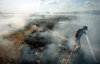 JEROME A. POLLOS/Press..Lance Deacon saturates the edge of a field fire Tuesday, August 15, 2006 near Rathdrum, Idaho during the first day of bluegrass field burning held by farmers on the Rathdrum Prairie.