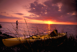 Stock photo of a man with his kayak on shore wading out and flyfishing in the bay at sunset