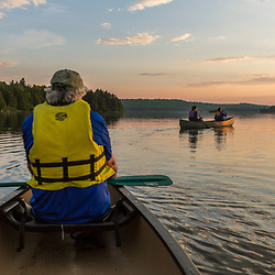 A man and two women canoe on Long Pond near the Appalachian Mountain Club's Gorman Chairback Lodge. Maine's 100 Mile Wilderness.
